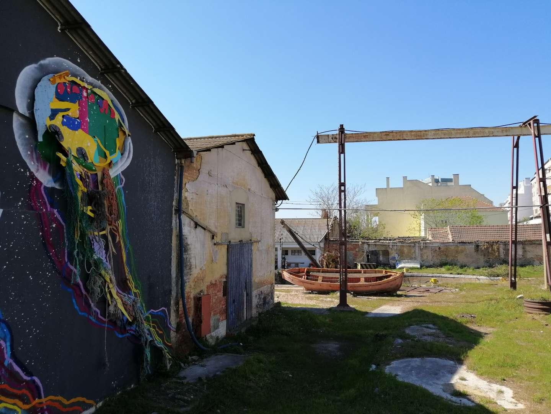 Calle abierta de Barreiro con casas en ruinas, un bote abandonado y una pintada colorida en una pared.