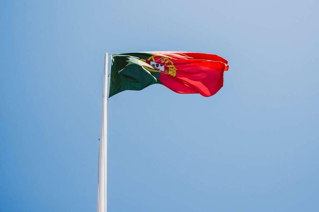Bandera de Portugal ondeando en un asta con un cielo azul despejado.
