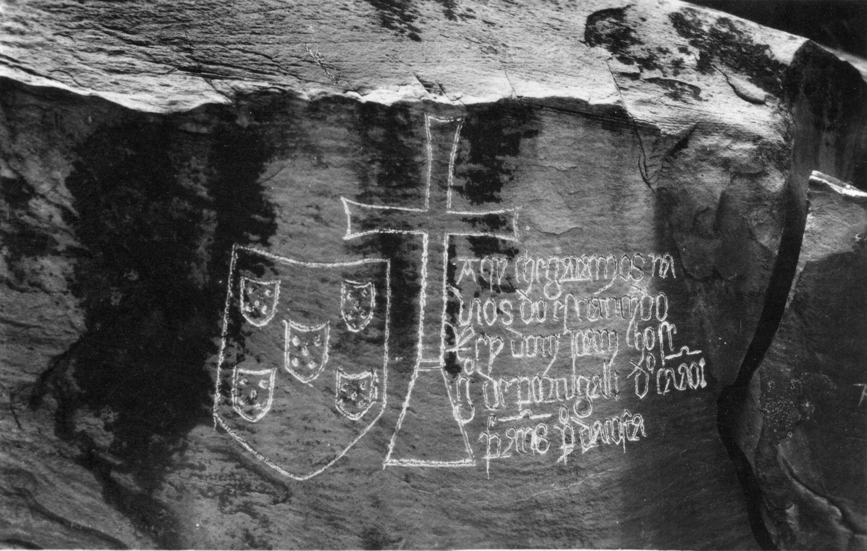 Antigua fotografía de la inscripción de Yellala en blanco y negro mostrando un escudo, una cruz cristiana y nombres de exploradores portugueses.
