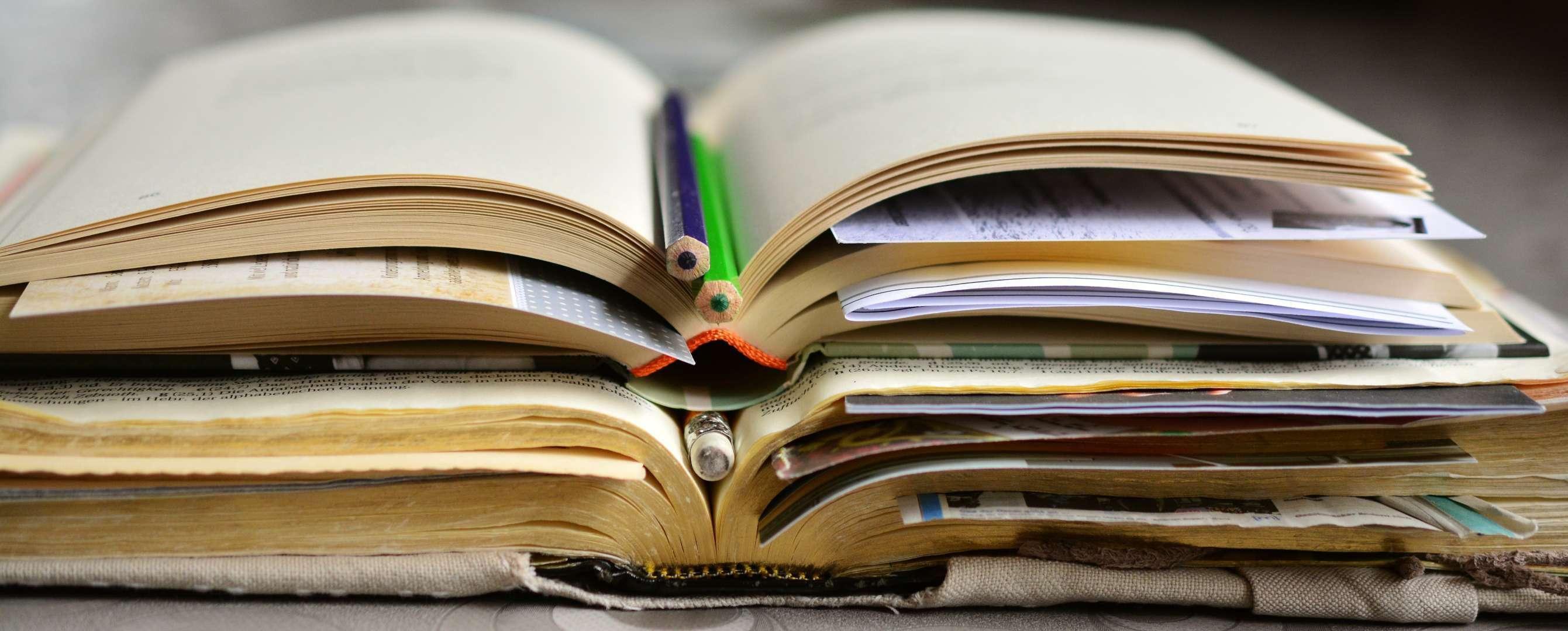 Libros abiertos unos encima de otros con lápices.