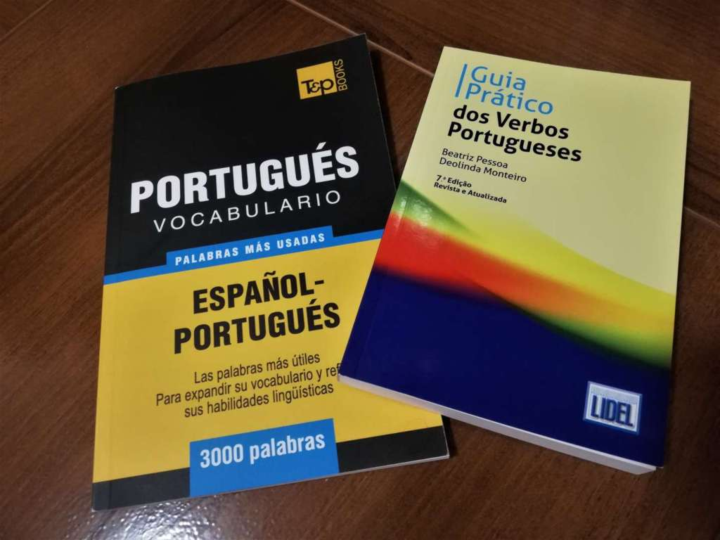 Un libro de vocabulario y una guía de verbos para aprender portugués.