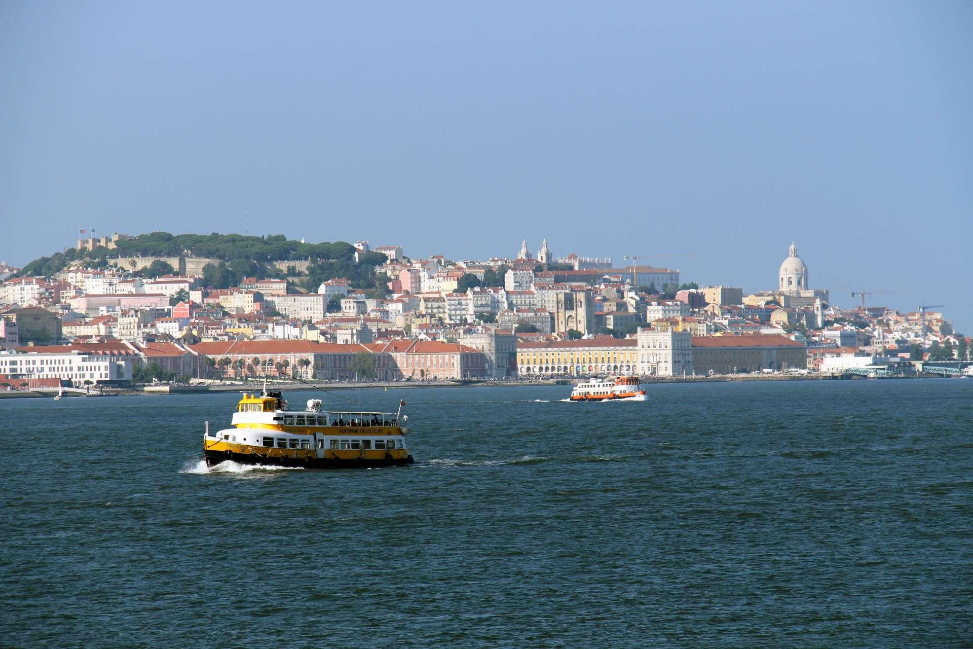 El Río Tajo con barcos surcando las aguas y Lisboa al otro lado.