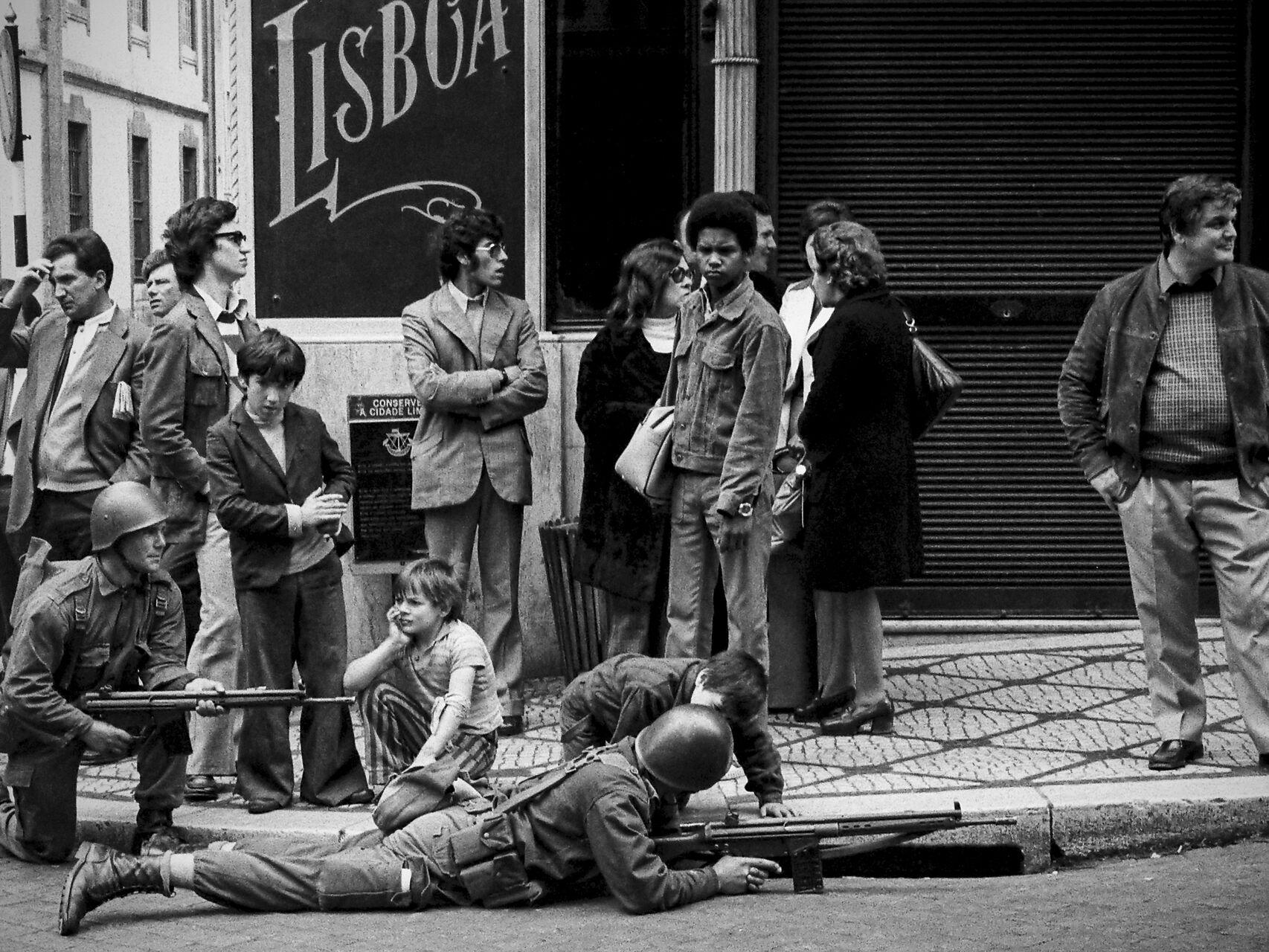 Soldados del 25 de abril atentos en una calle con el pueblo alrededor.