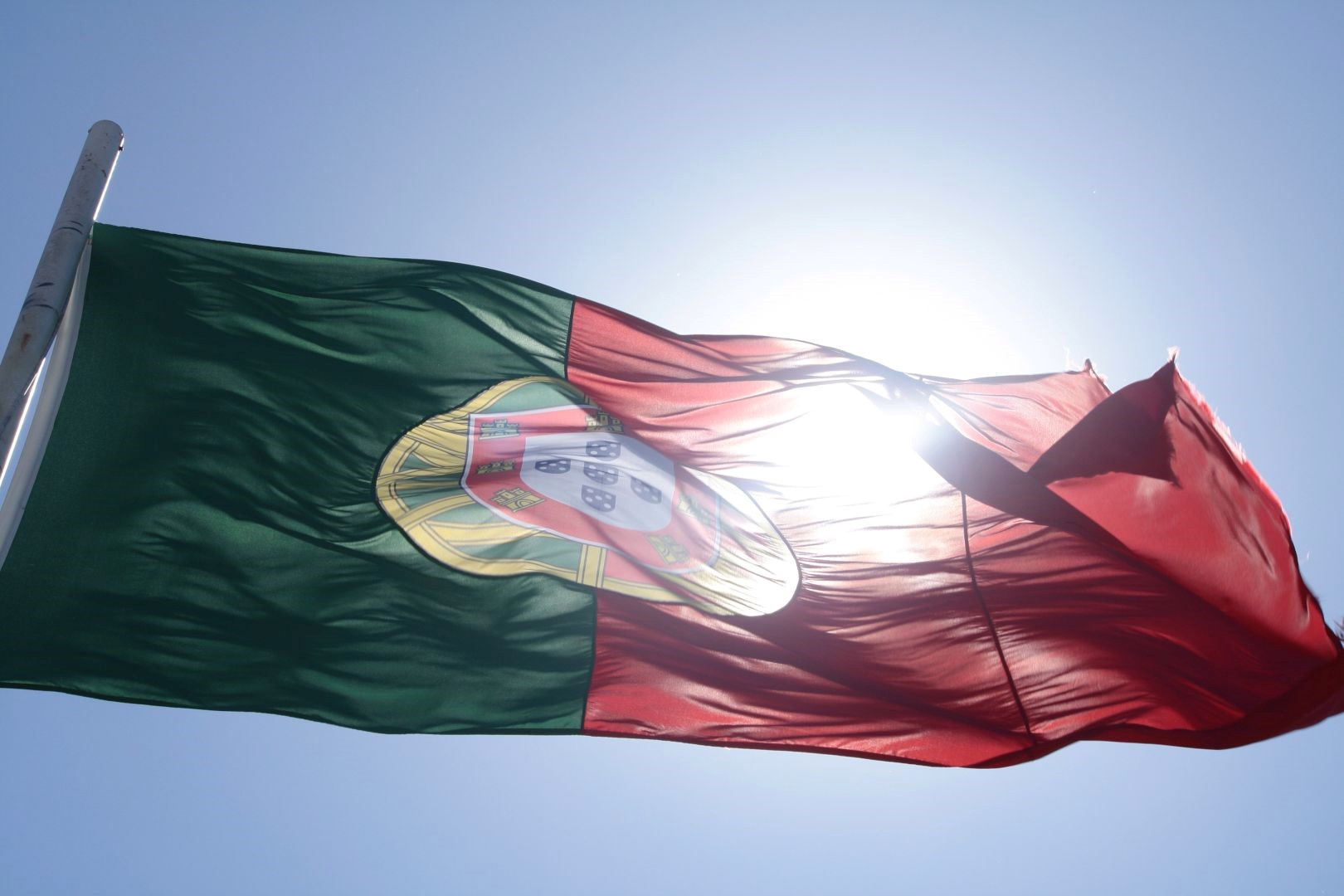 Bandera de Portugal con un cielo azul y el sol de frente.